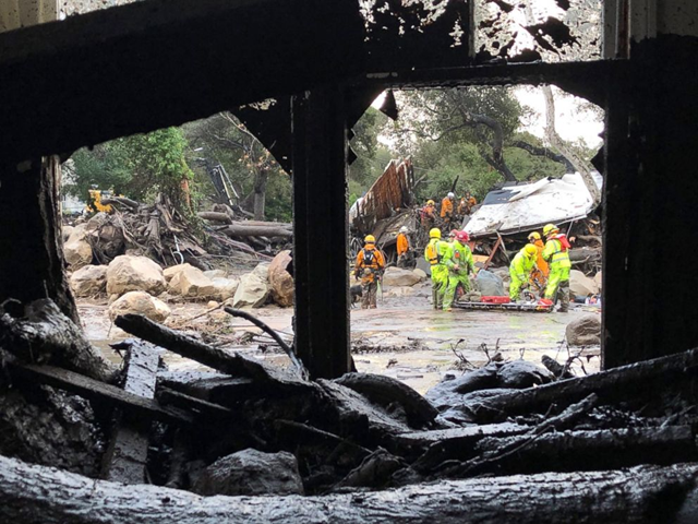 Firefighters search for trapped people in Montecito, California on 9 January 2018, after mud and debris destroyed buildings following heavy rains. Photo: Mike Eliason