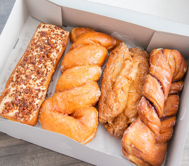photo of a Maple Bacon Bar, Glazed Twist, Buttermilk Bar, and Cinnamon Twist in a doughnut box