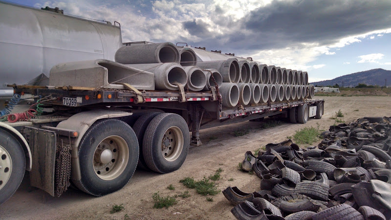 flatbed trailer loaded with large cement pipes