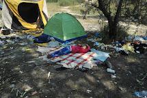 Děvče z Afghánistánu odpočívá na dece v opuštěné cihelně v srbské Subotici. Už tu žije s rodiči přes týden. Došly jim peníze a nemají z čeho zaplatit další cestu. (Foto: Iva Zímová pro ČvT)