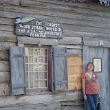 Carrie in front of schoolhouse.