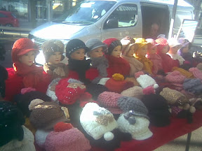 market stall with row of hats on dummy heads