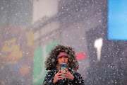 A woman uses her phone to take photos during a snowstorm in Times Square, as record low temperatures spread across the Midwest and Eastern states, in New York City, US, January 30, 2019.