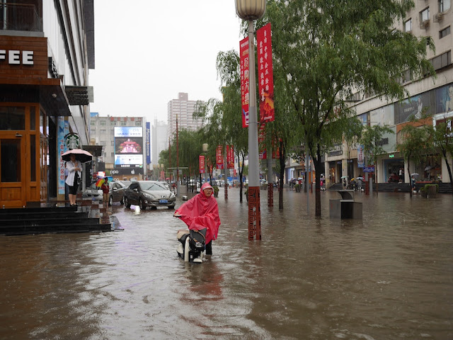 woman pushing scooter on a flooded street in Taiyuan, China