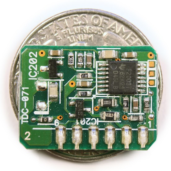 The microcontroller circuit board from an 85W Macbook power supply, on top of a quarter. The MPS430 processor monitors the charger's voltage and current.