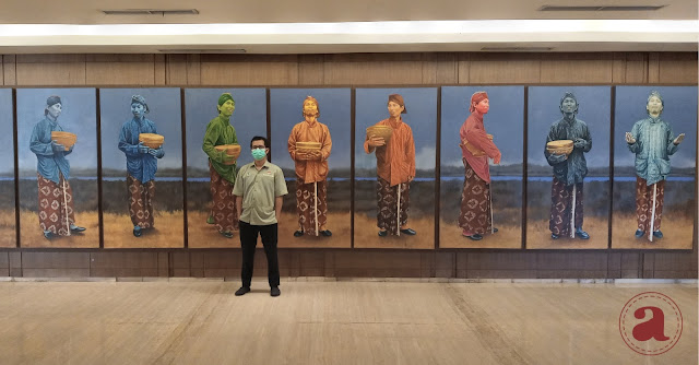 Berfoto di depan lukisan