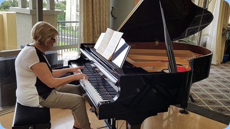 Kay Boyes playing the Village's Kawai grand piano.