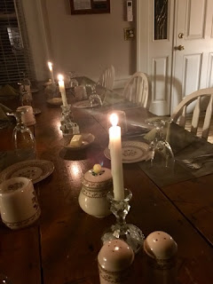 lit white candles on a wood plank table with antique china