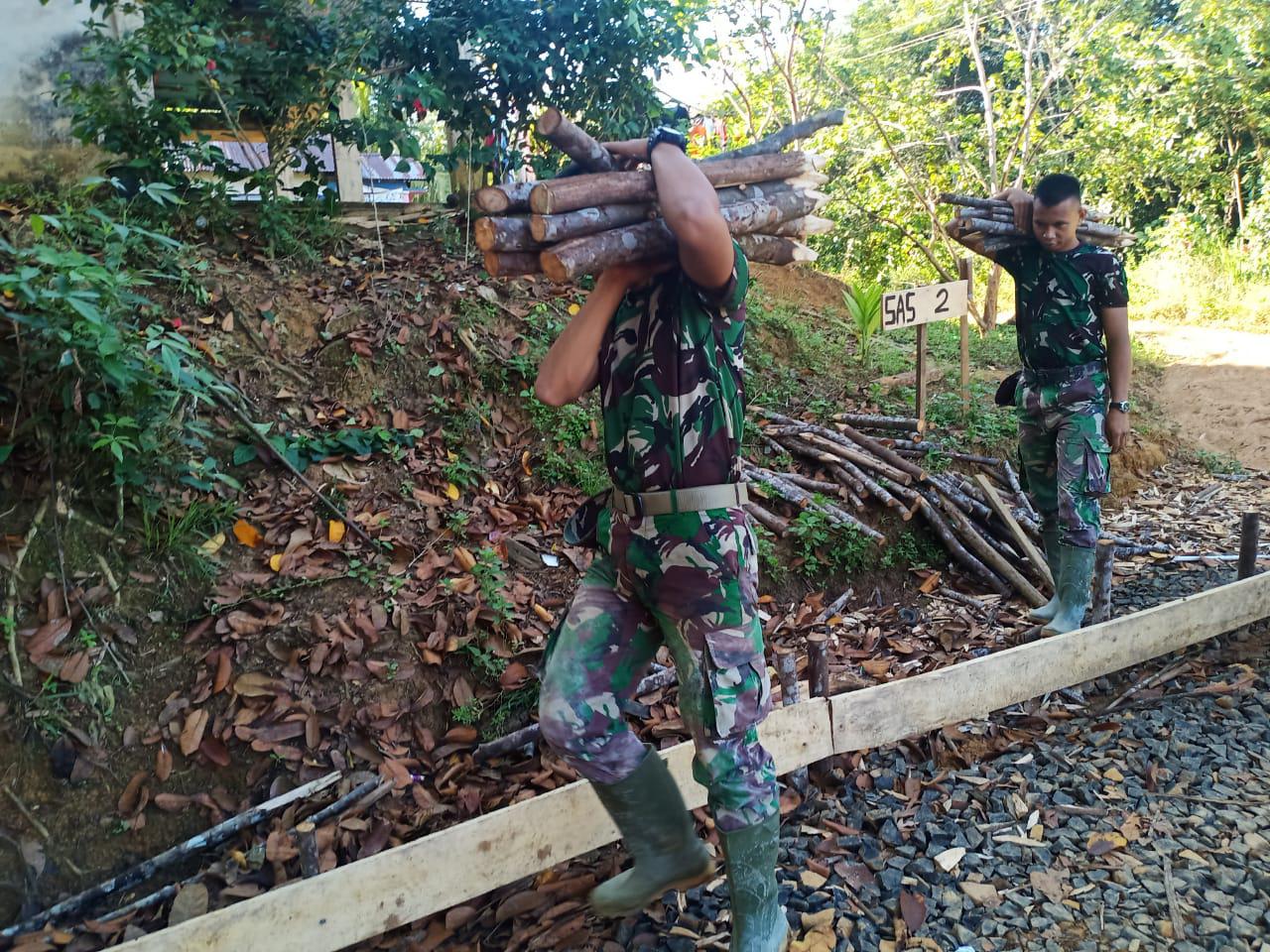 Anggota satgas TMMD siapkan kayu untuk bahan bakar memasak.