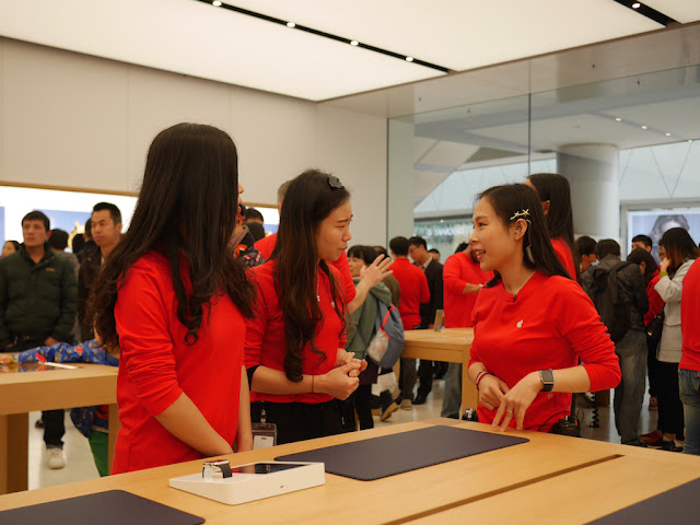 three employees speaking to each other at the SM Lifestyle Center Apple Store in Xiamen, China