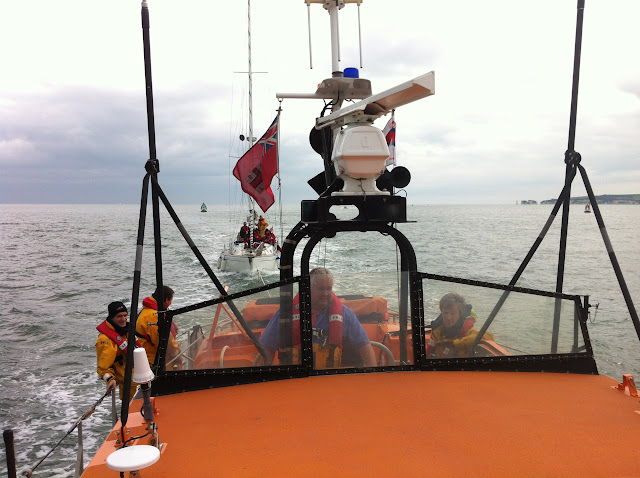 8 April 2012: Coxswain Jonathan Clark at the helm and other crew members on deck of the Tyne class lifeboat towing a yacht into Poole Harbour. Photo: RNLI Poole Dave Riley