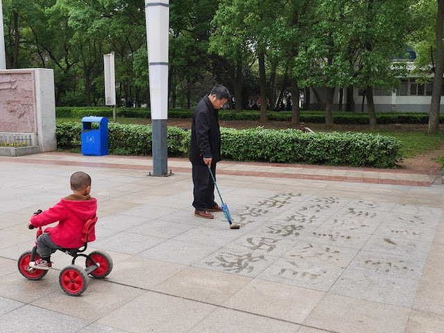 child on tricycle rides by a man doing water calligraphy