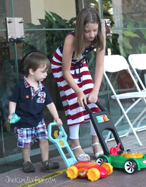Kids with toy lawnmowers
