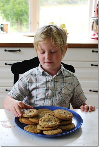Sebastian hugger in på kakfatet, redo att smaka en nybakad kaka.