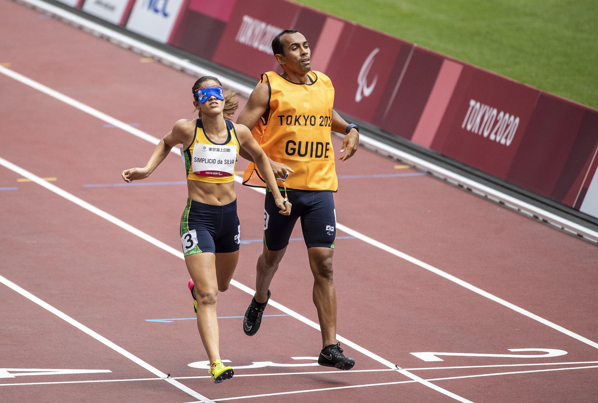 De shorts preto e camisa amarela, Talita Simplício e o guia Felipe Caetano cruzam a linha de chegada