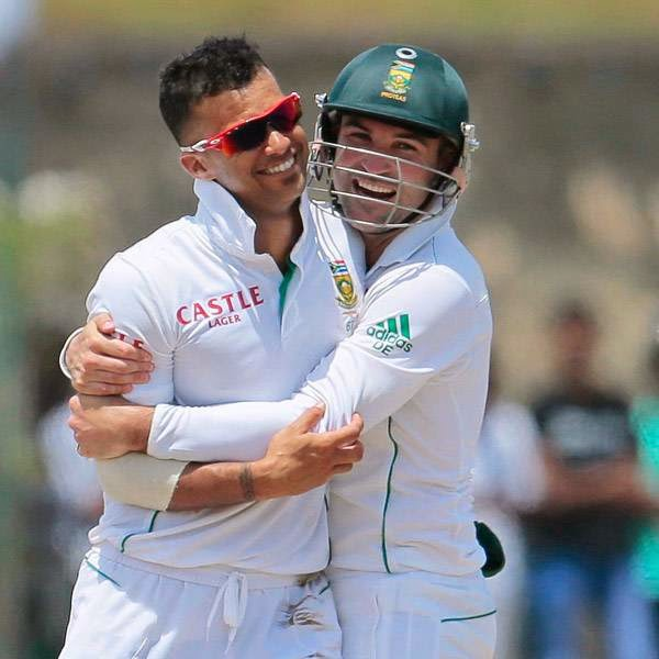 South African cricketer Dean Elgar, right, hugs bowler Jean-Paul Duminy as they celebrate the wicket of Sri Lanka's Kumar Sangakkara during the fifth day of the first test cricket match in Galle, Sri Lanka, Sunday, July 20, 2014.