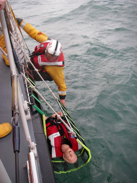 Crew Member Scott Rowland guiding the casualty in the Jason's Cradle onto Poole's all-weather lifeboat. Photo: RNLI Poole/Anne Millman