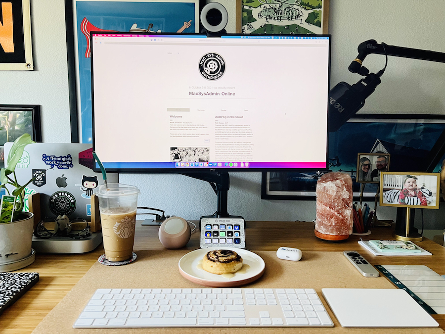 Picture of a desk and monitor with the MacSysAdmin website pulled up. On the desk is an iced coffee, cinnamon roll, and keyboard and trackpad. Photo by author.