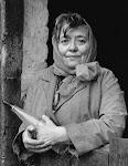 vrouw met sjaaltje om hoofd en fles in de hand leunend op onderdeur