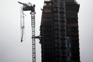 NEW YORK, NY - OCTOBER 29: Part of a crane boom is seen hanging off a building under construction on West 57th Street on October 29, 2012 in Manhattan, New York City. The storm, which threatens 50 million people in the eastern third of the U.S., is expected to bring days of rain, high winds and possibly heavy snow. New York Governor Andrew Cuomo announced the closure of all New York City will bus, subway and commuter rail service as of Sunday evening. (Photo by Allison Joyce/Getty Images)