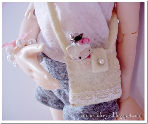A Hello Kitty phone charm peeking out from inside a doll's purse.