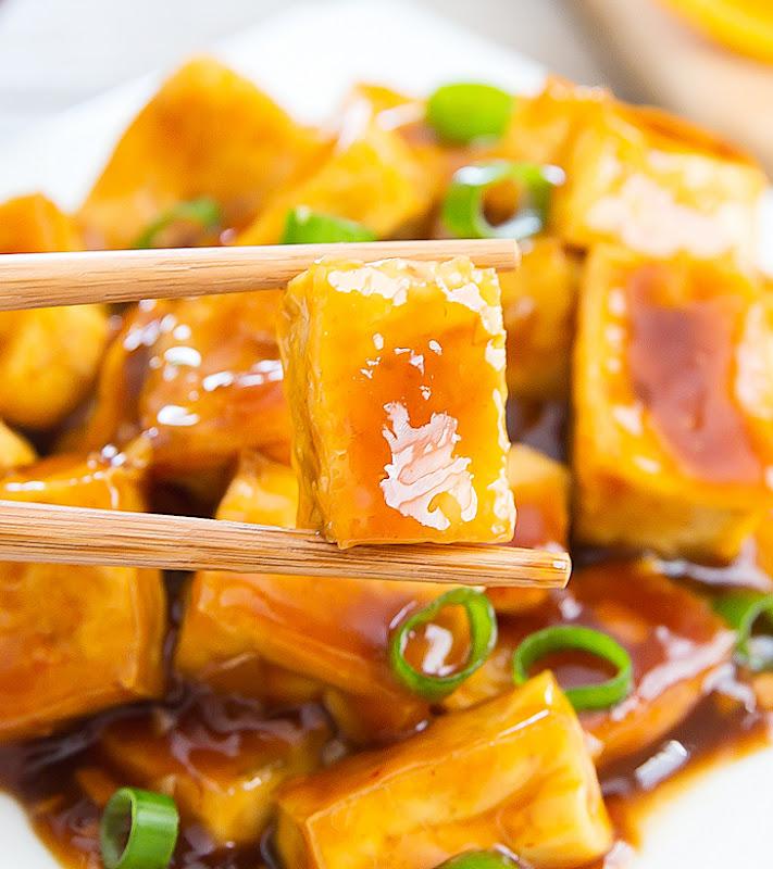 a close up of chopsticks holding crispy baked orange tofu