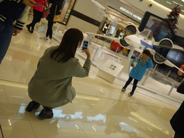 woman photographing a child in front of an X-wing fighter at the IAPM shopping center in Shanghai
