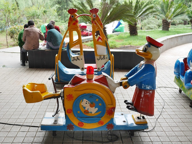 kiddie ride resembling half a seesaw with a duck character holding one end end to push it up and down