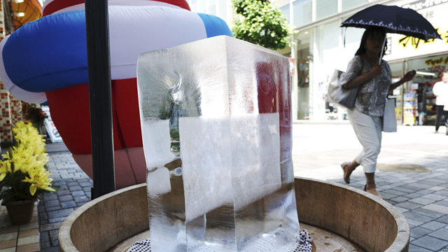 A block of ice is placed at a pedestrian street to cool down the spot in Tokyo Friday, 20 July 2018. Thirty people have died with the high temperatures and thousands have been rushed to the hospital across the country. Photo: VOA News