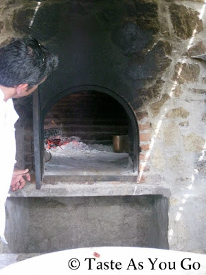 Chef Enrique Silva Peeks into the Wood-Burning Oven at Los Tamarindos in Los Cabos, Mexico - Photo by Taste As You Go