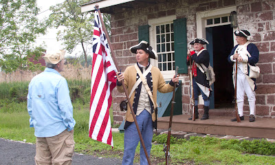 Andy Anderson checks out the original colonial flag shown by Arthur Greene ( a distant relative of Colonial General Nathenial Greene). The flag is the earliest known Continental flag in front of the Demerest house. Arthur said that the Betsey Ross flag with the stars in a circle did not exist.