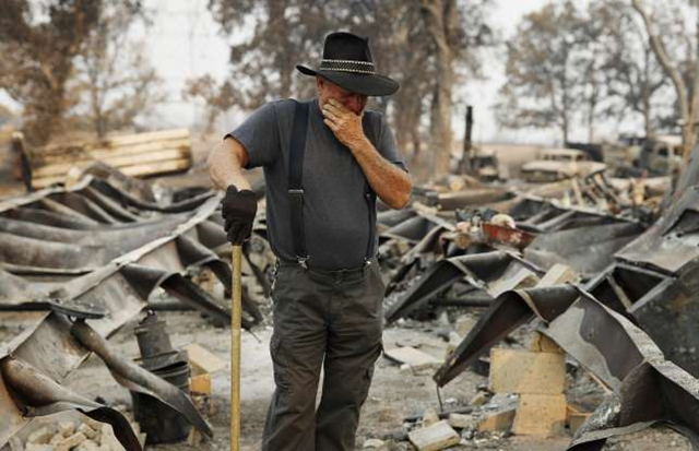 Ed Bledsoe tries to hold back tears as he searches through what remains of his home on 13 August 2018, in Redding, California. Photo: John Locher / AP Photo
