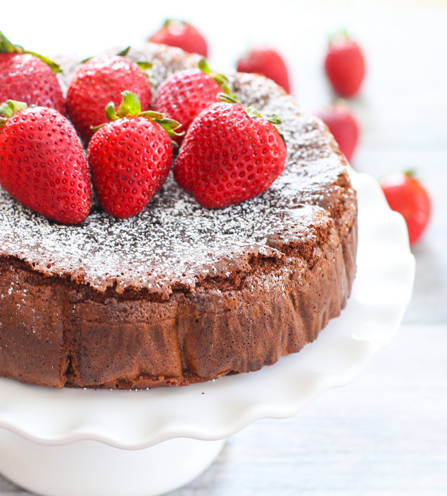photo of Flourless Nutella Cake garnished with powdered sugar and fresh strawberries