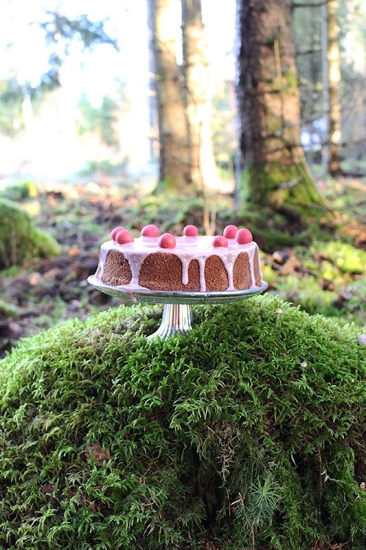En mörk sockerkaka med smak av glögg står på ett tårtfat av glas på en liten kulle av grön mossa mitt ute i skogen.