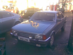 large silver car with town monument reflection on bonnet