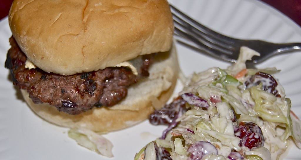 sirloin cherry burger with melted brie on a bun sitting on a plate beside a pile of cherry coleslaw