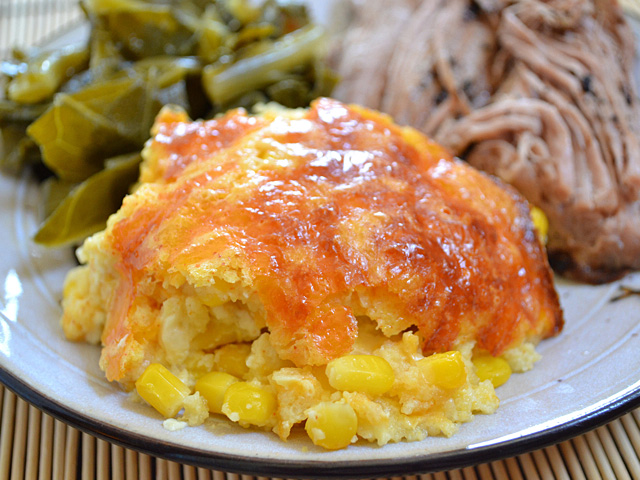 Corn and Cheddar Pudding on plate with main dish