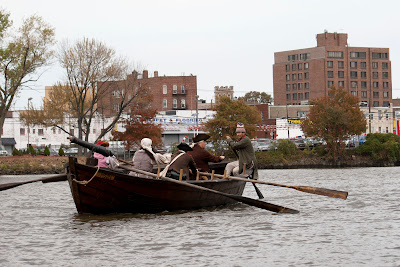 Passing the home of Tom Hart Photo where these very words are being typed (2nd window from top and left), RE-ENACTORS ON  BATTOE 'MOON' ON THE HACKENSACK RIVER. Photos by TOM HART/  FREELANCE PHOTOGRAPHER.