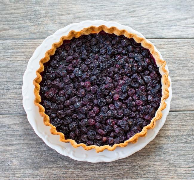overhead photo of an unsliced blueberry tart