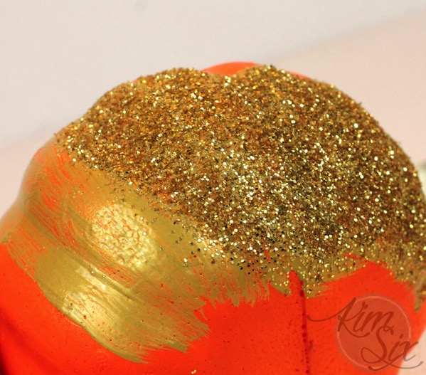 Adding glitter to styrofoam pumpkin