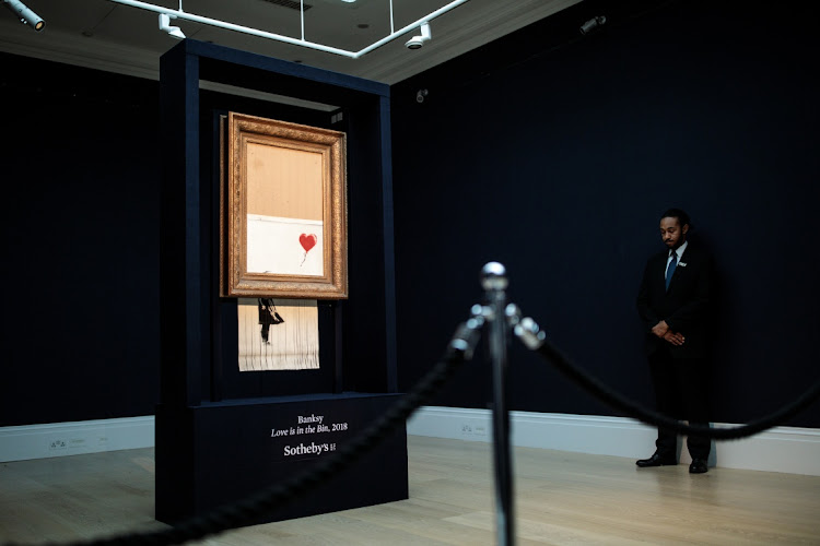 A security guard stands next to 'Love is in the Bin' by British artist Banksy during a media preview at Sotheby's auction house on October 12, 2018 in London, United Kingdom. During Sotheby's Contemporary Art Sale on 5th October the Banksy artwork 'Girl with Balloon' shredded through the bottom of the frame as it was sold. With Banksy being responsible for the shredding, the buyer has agreed to proceed with the sale and it is now titled 'Love is in the Bin' and said to be worth more than the £1.04million paid. Picture: GETTY IMAGES/ JACK TAYLOR