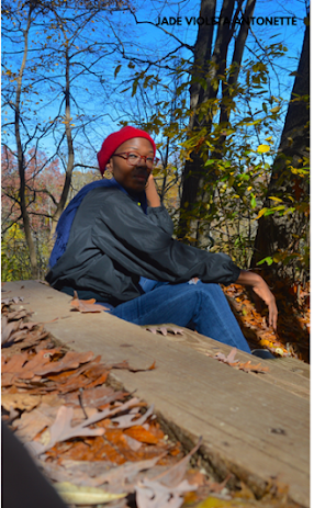 Jade Violeta Antonette, a dark-skinned Black person, sits on top of a wooden staircase outdoors with a shadow over her face. She is wearing a black top, blue jeans, and a red beret. There are trees with changing leaves in the background.