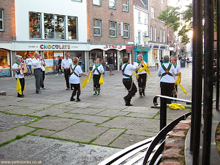 Morris dancers, June 2013, across the weedy raised area to the apparently functional stone paving in the main area. No one tripping over.