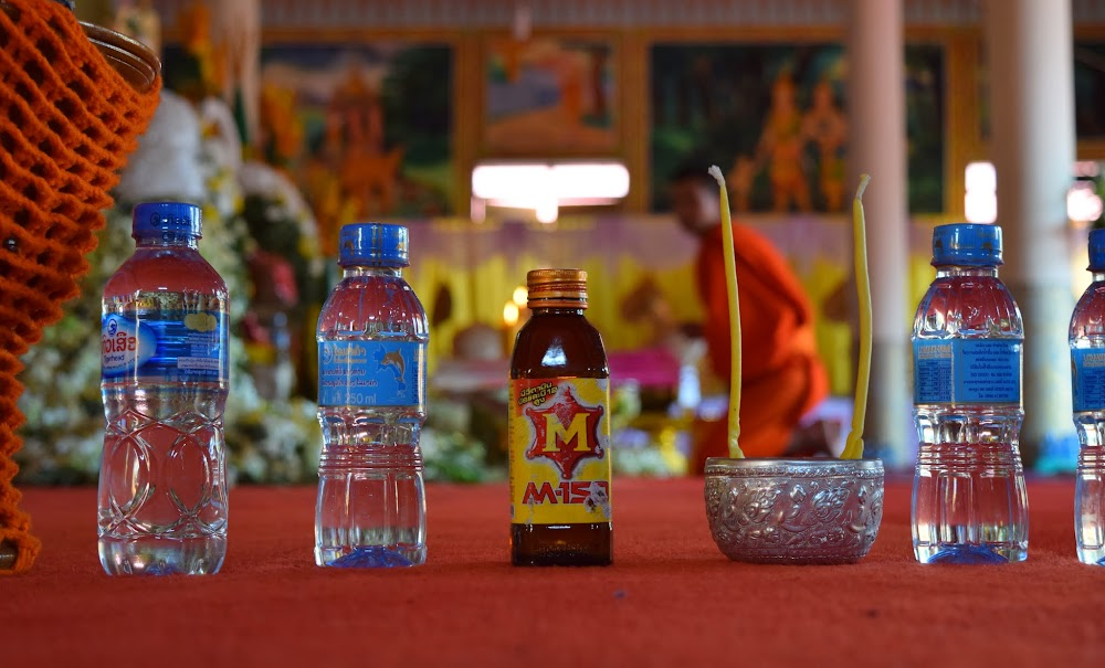 offerings on the floor of this temple... including my beloved M-150 energy drink.