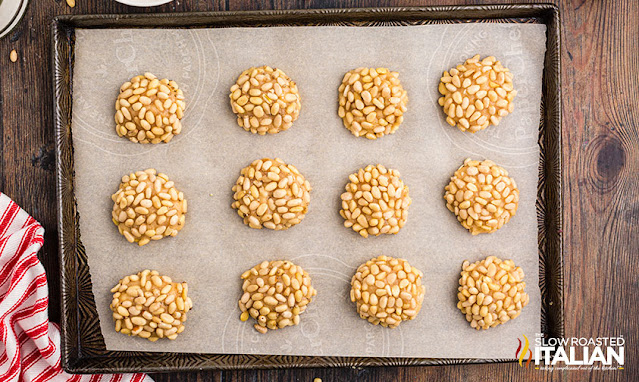 pine nut cookies rolled on a baking sheet
