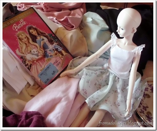 ball jointed doll staring at a Barbie DVD