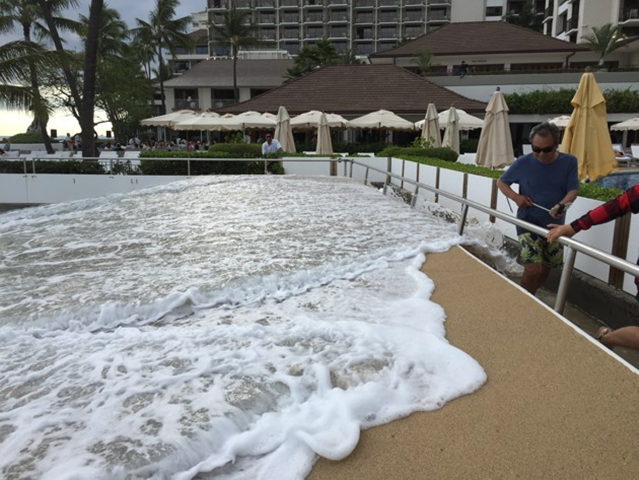 An unbelievable sight for those who know what the Halekulani Hotel walkway normally looks like: Sand is packed up to the top of the wall and ocean water spills over it. Photo: gonserm / Hawaiʻi and Pacific Islands King Tides Project