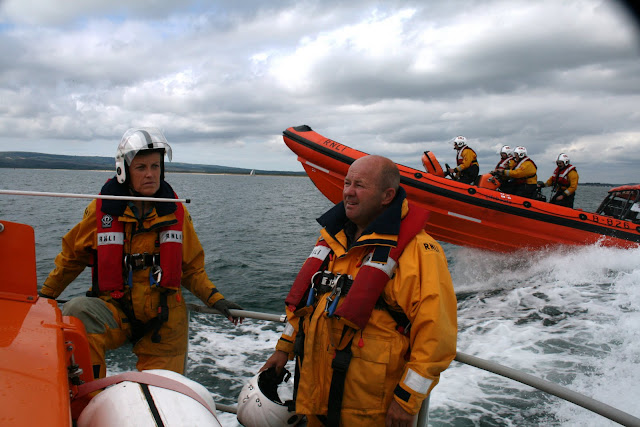 Crew relaxing after a helicopter exercise, with the B class Atlantic 85 inshore lifeboat heading off