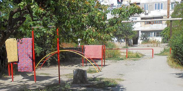 Spielgeräte als Teppichstangen in einem Hinterhof in Osch, Kirgistan