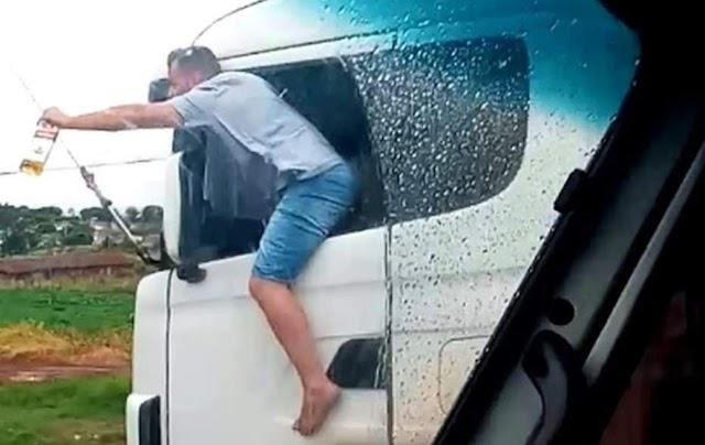 Caminhoneiro é filmado com corpo para fora de veículo com garrafa de bebida na mão enquanto dirige